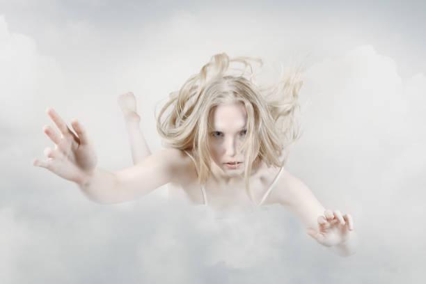 Una joven flotando a través de las nubes en el cielo. Relajación del alma - foto de stock
