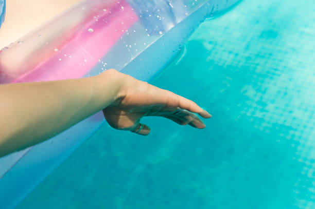 Young woman floating her hand in the swimming pool stock photo