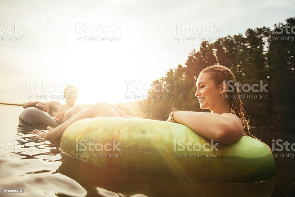 Young woman floating in an innertube at sunset stock photo