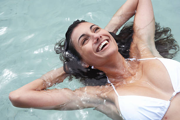 Young woman floating in sea, hands behind head, laughing, close-up stock photo