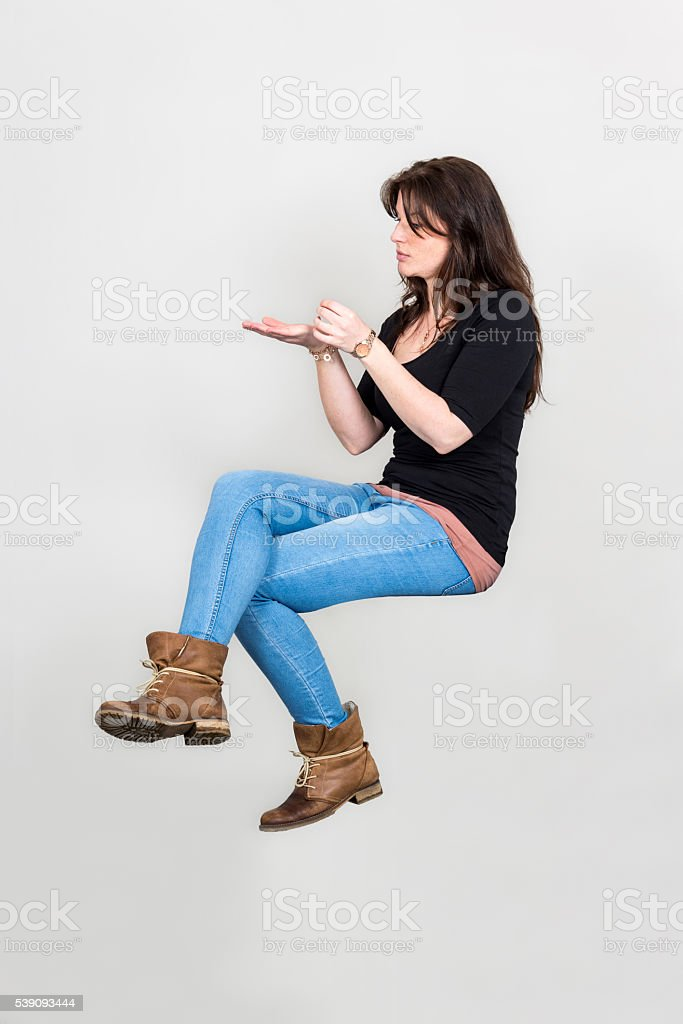 Young woman floating in sitting position with presenting gesture stock photo