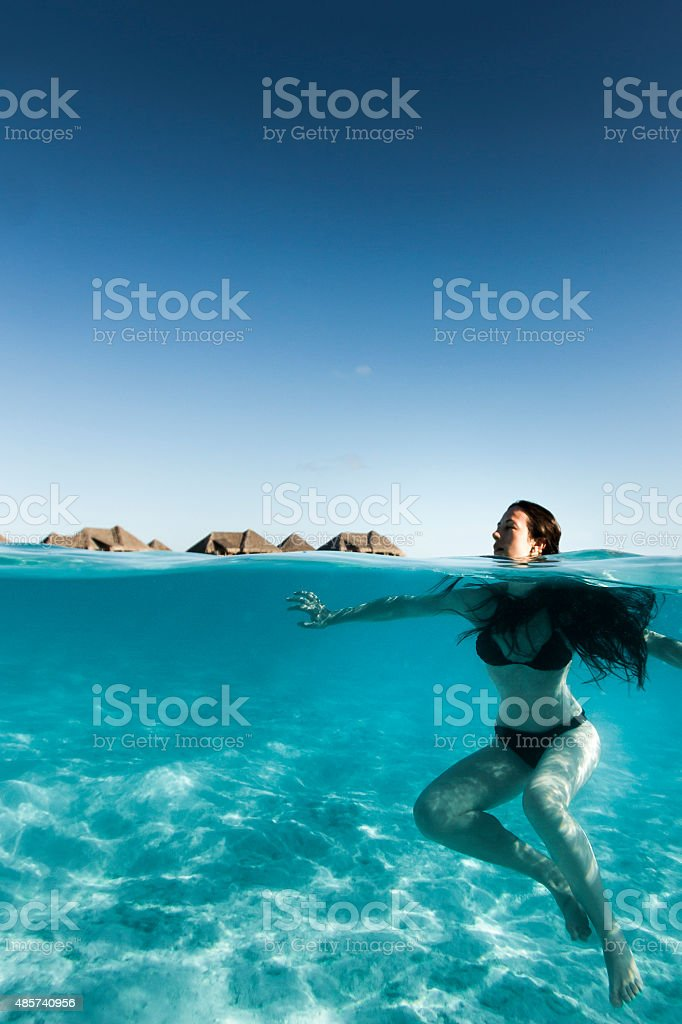 Young Woman Floating in Turquoise Clear Water in Bora Bora stock photo