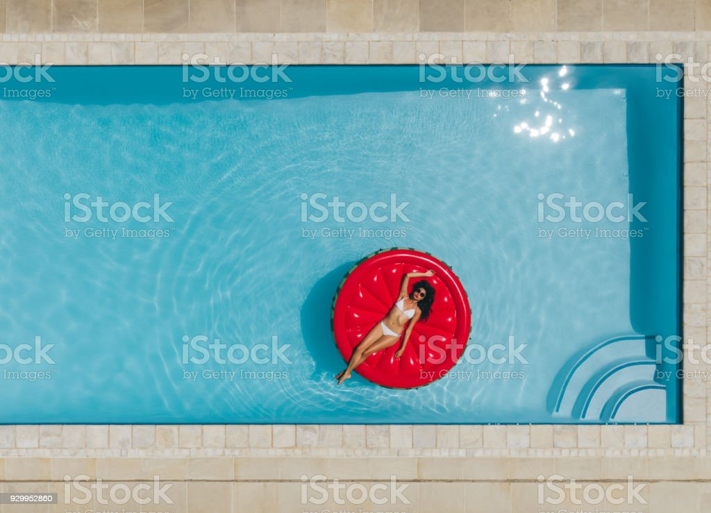 Young woman floating on inflatable mattress in pool – zdjęcie