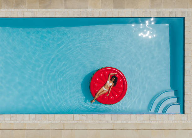 Young woman floating on inflatable mattress in pool stock photo
