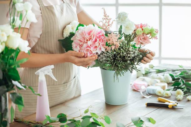 jonge vrouw bloemist bezetting werken met bloemen - bloemstuk stockfoto's en -beelden