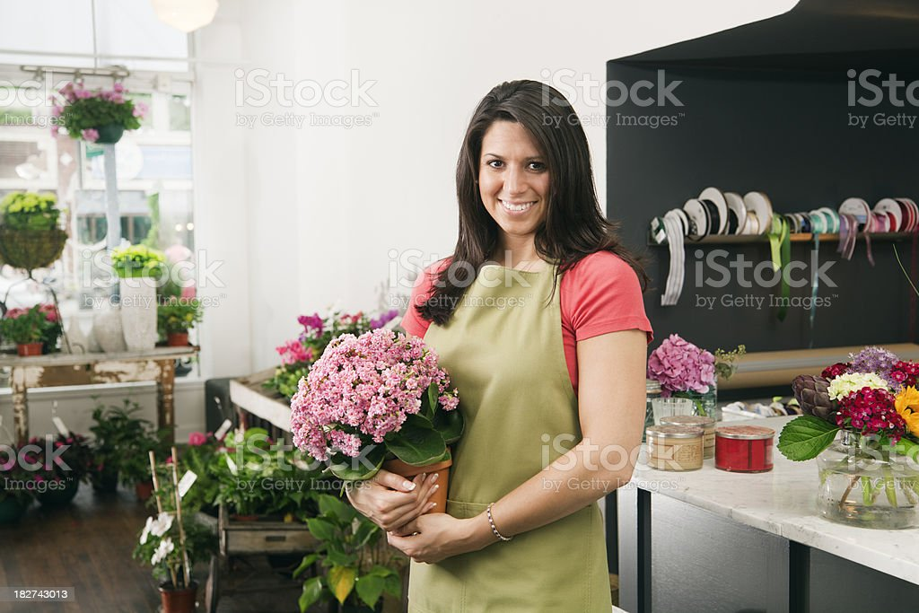 \'Subject: Horizontal view of a young woman florist clerk holding a...