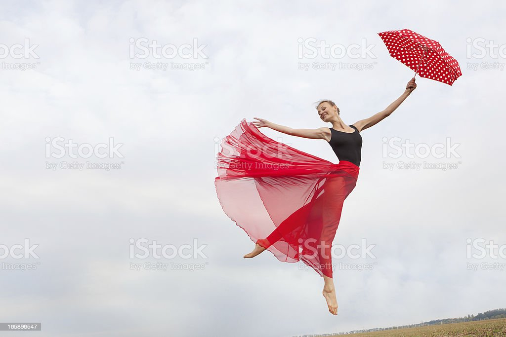 Young Woman Flying in the Sky with Umbrella royalty-free stock photo