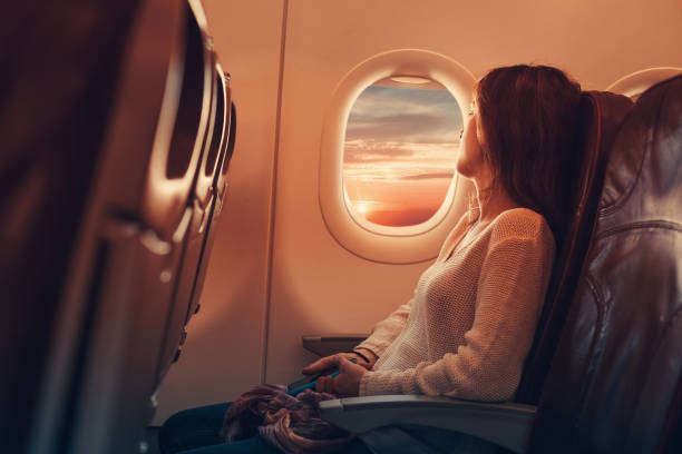 Young woman flying to France Woman in airplane looking through the window passenger stock pictures, royalty-free photos & images