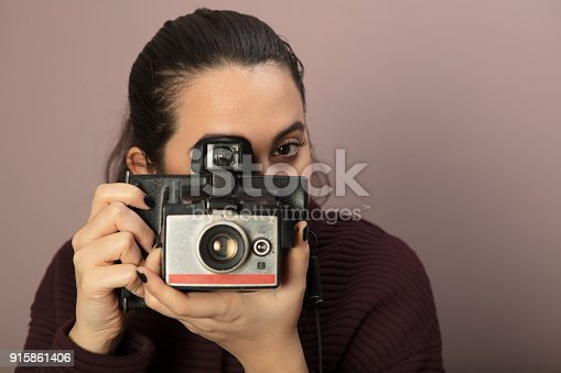 Young woman focusing on the viewer and taking picture with a vintage camera