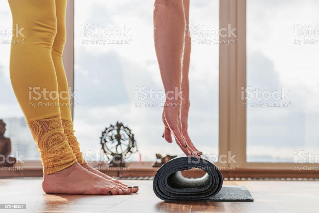 Young woman folding fitness mat stock photo