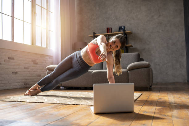 Young woman follows with a laptop a gym exercises. She is at home due to coronavirus codiv-19 quarantine stock photo