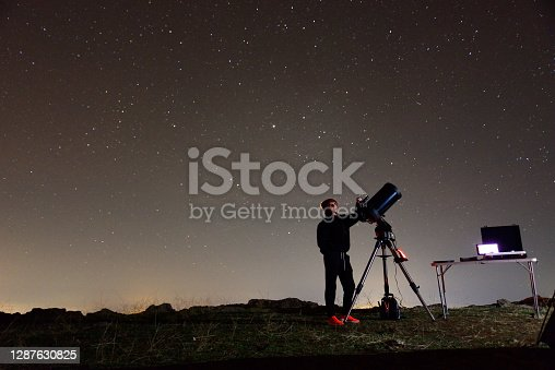 Young woman fond of astronomy observing through her telescope