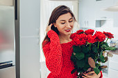 Young woman found red roses on kitchen. Happy girl smelling flowers. Women's day surprise