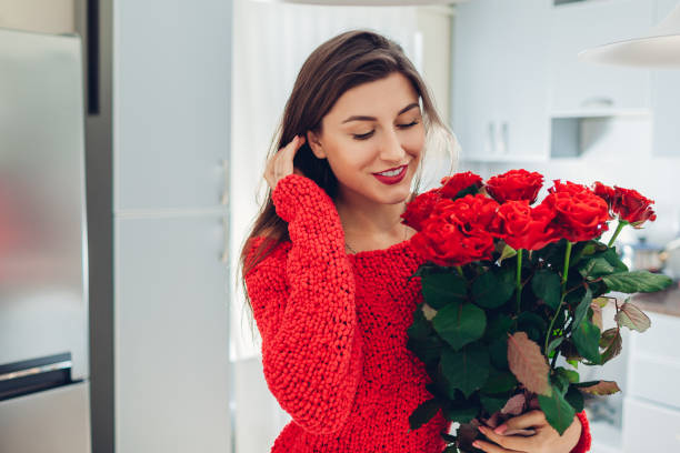 young woman found red roses on kitchen. happy girl smelling flowers. women's day - womens day stock photos and pictures