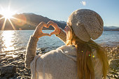 istock Young woman framing beautiful landscape into heart shape 626678756