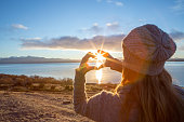Young woman standing by the lake makes a heart shape finger frame over the sunrise. Shot at lake Pukaki in Mount Cook national park, New Zealand.