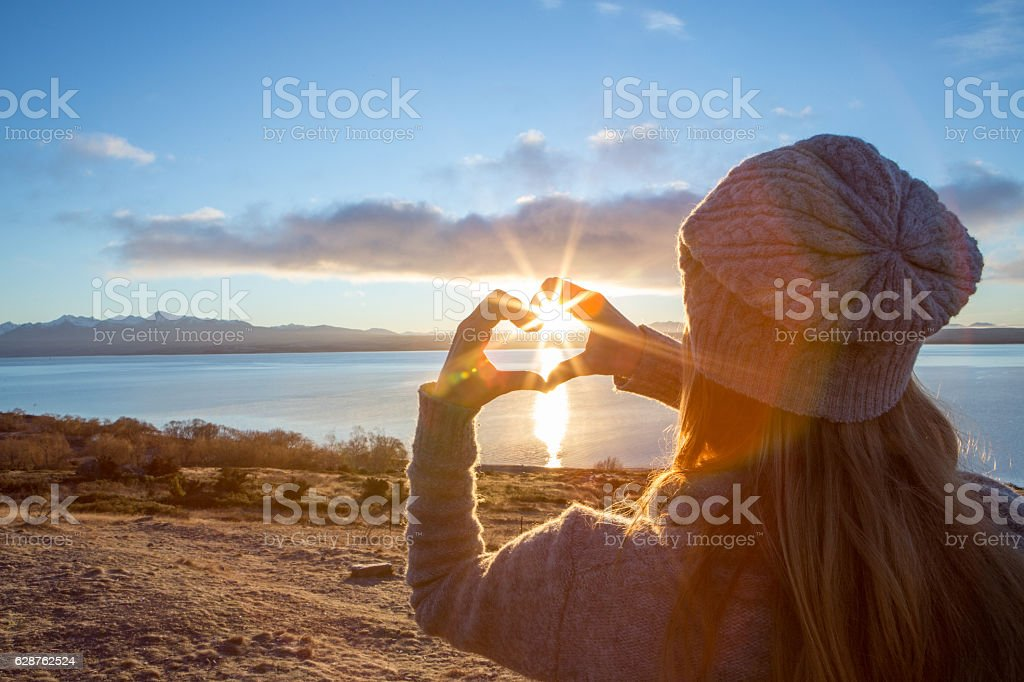Young woman framing sunrise into heart shape finger frame stock photo