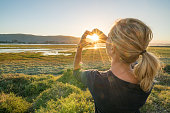 One young woman makes a heart shape finger frame on the sunset. Travel people concept.