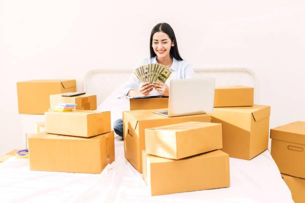 junge frau freiberufler arbeiten und halten geld mit pappkarton auf bett zu hause - kmu business online und lieferung-konzept - geld schön verpacken stock-fotos und bilder