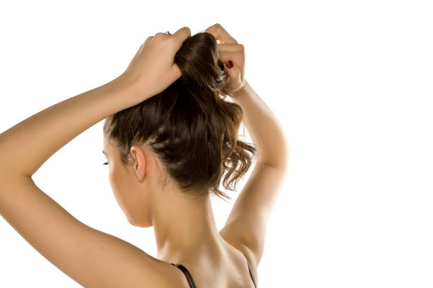 Young woman from behind,  tying her hair on white background stock photo