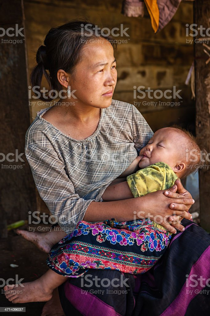 Young woman from the hill tribe breastfeeding her baby stock photo