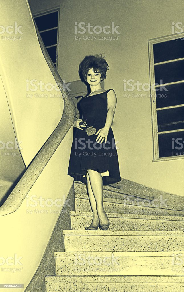 Young woman from the sixties coming down the stairs stock photo