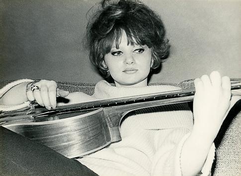 Vintage black and white photo from the sixties of a young woman playing guitar.