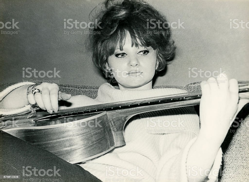 Young woman from the sixties playing guitar - Photo