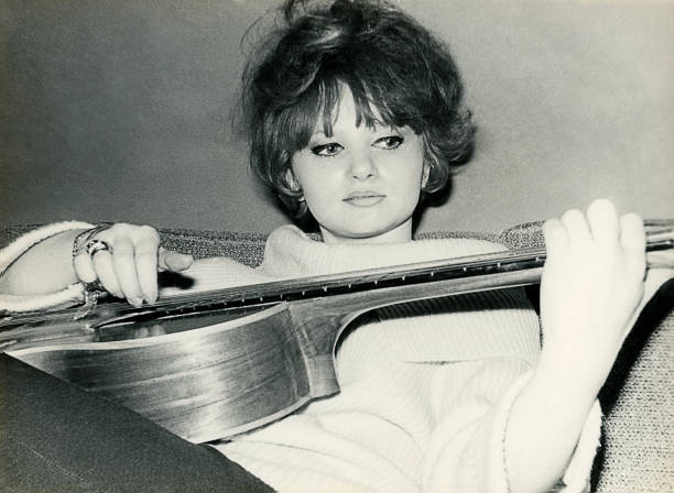 Young woman from the sixties playing guitar - foto de acervo