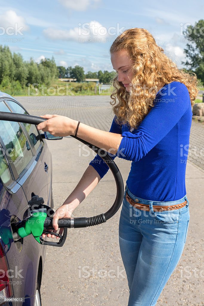 Young woman fueling car tank with gasoline stock photo