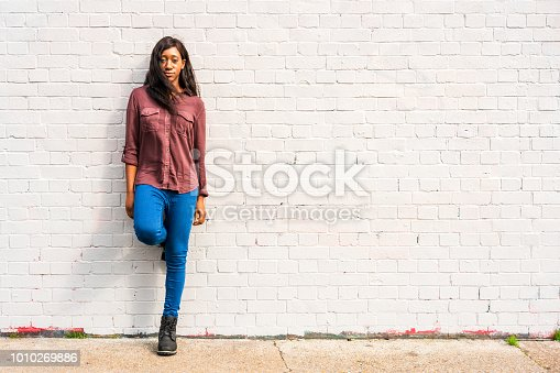 A young woman leaning against a brick wall in East London.