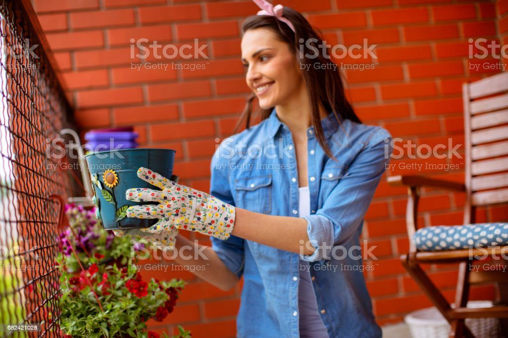 Young woman gardening on a balcony royalty-free stock photo
