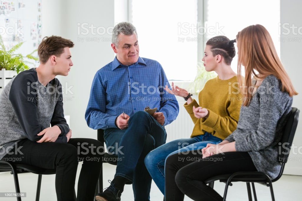Young woman gesturing during mental group therapy Young woman gesturing during mental group therapy in lecture hall. Students are with social worker during meeting. They are at university. 18-19 Years Stock Photo