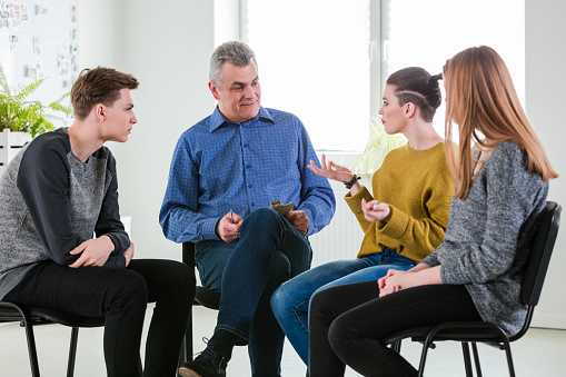 Young Woman Gesturing During Mental Group Therapy Stock Photo - Download Image Now