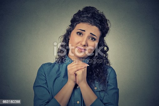 Closeup portrait young woman gesturing with clasped hands, please forgive me pretty please with sugar on top isolated gray background. Human emotion facial expression feeling sign symbol body language