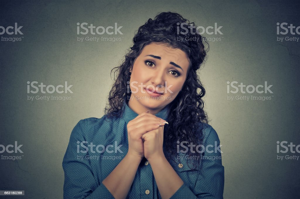 young woman gesturing with clasped hands, please forgive me stock photo