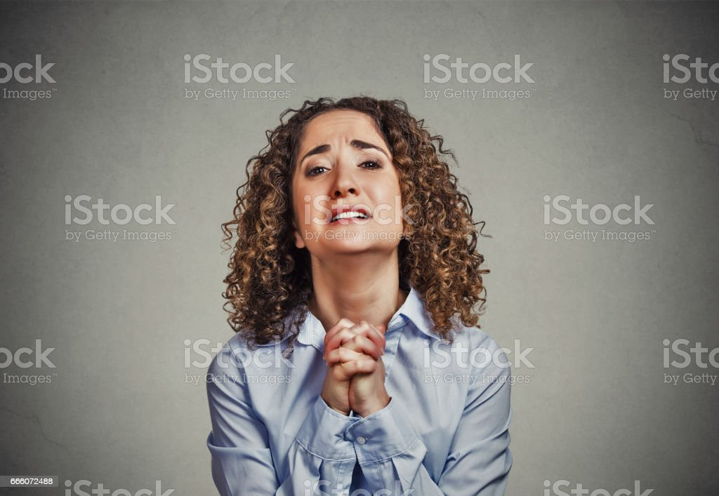 young woman gesturing with clasped hands, pretty please stock photo