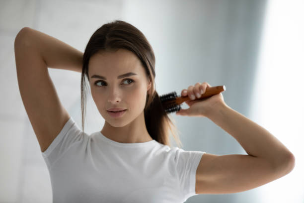 Young woman get ready brush hair in bathroom Young beautiful woman look in mirror brush long healthy brunette hair, millennial female do morning beauty routine in bathroom experiment with hairstyle, restoration mask, haircare concept long hair stock pictures, royalty-free photos & images