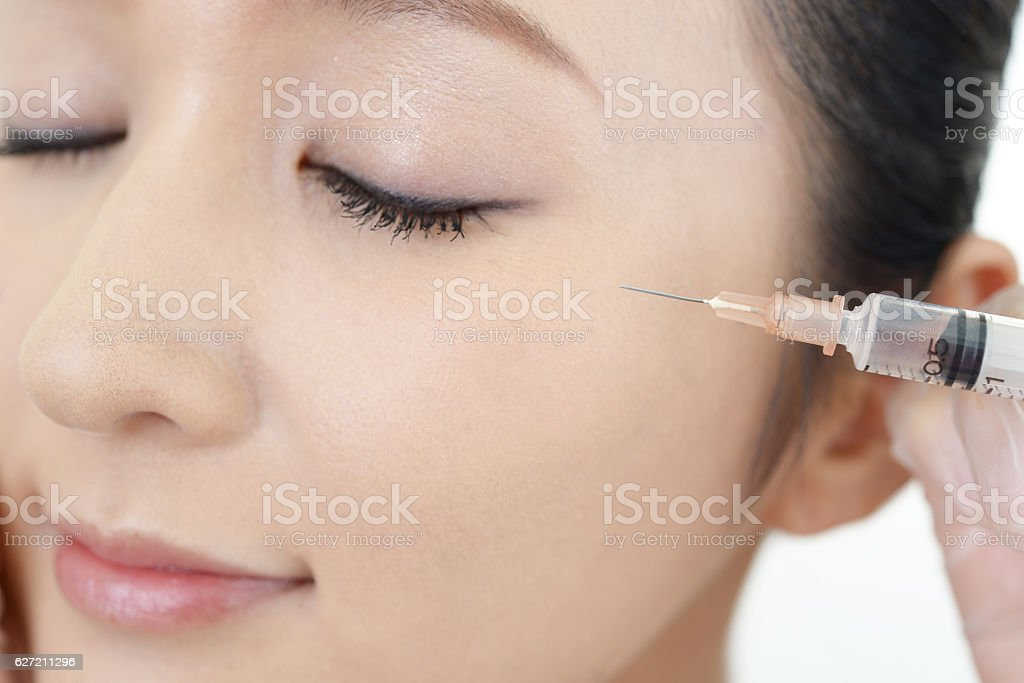 Young woman gets beauty injection in her face - Royalty-free Adult Stock Photo