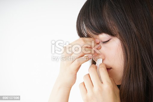 istock Young woman getting a bloody nose 696107596