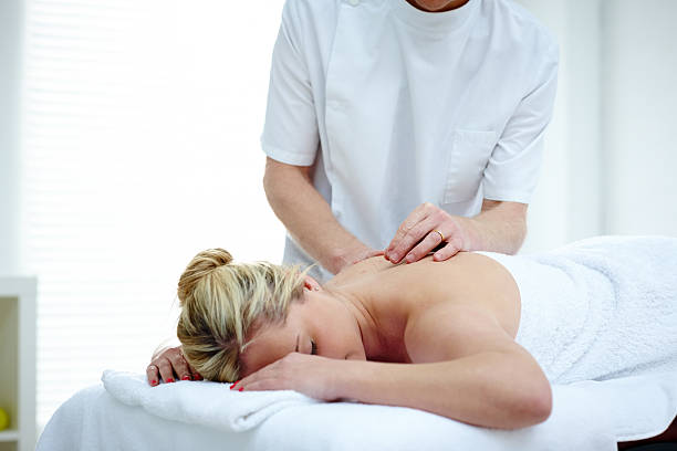Young woman getting acupuncture therapy from masseur stock photo