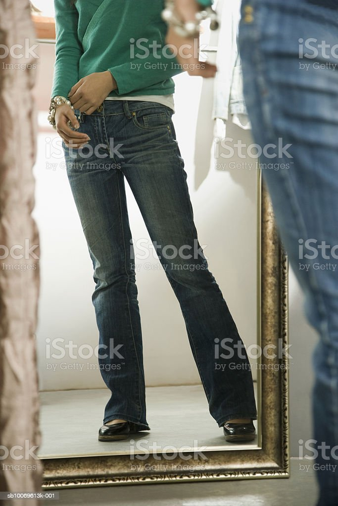 Young woman getting dressed in fitting room, low section foto de stock libre de derechos