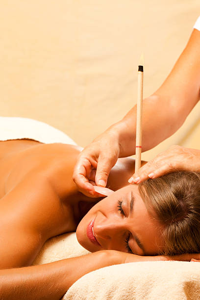a young woman getting ear candle therapy - hopi stock photos and pictures