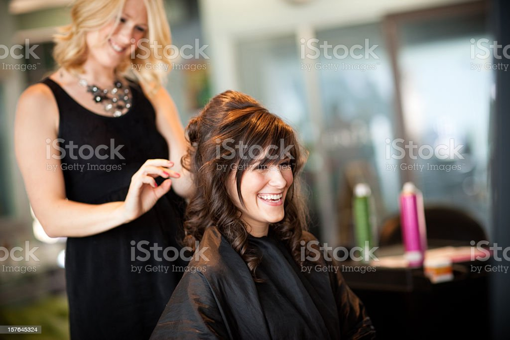 Young Woman Getting Hair Styled as Updo in Salon Color photo of a young woman getting her hair styled into an elegant updo in a salon. 20-24 Years Stock Photo