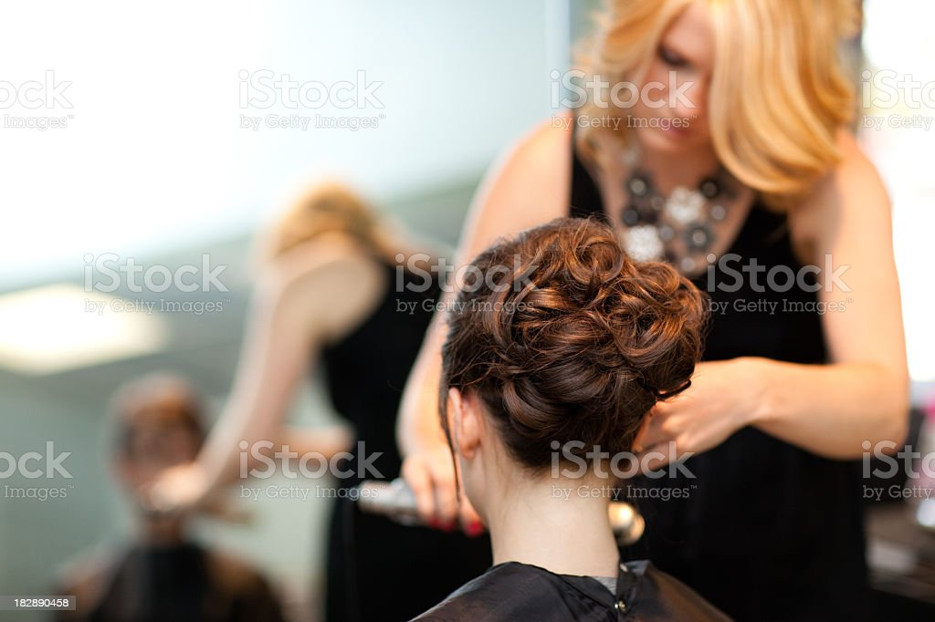 Young Woman Getting Hair Styled as Updo in Salon stock photo