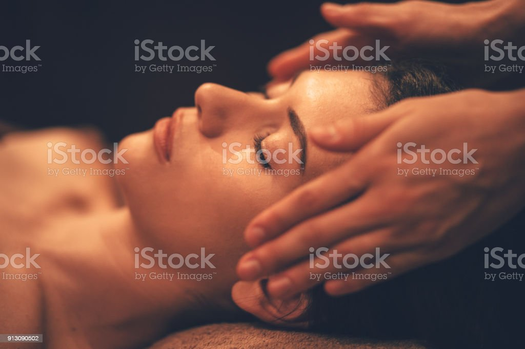 Young woman getting head massage at day spa salon stock photo