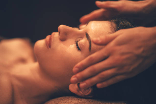 Young woman getting head massage at day spa salon Young brunette hispanic woman relaxing and getting facial massage from professional therapist at beauty salon massaging stock pictures, royalty-free photos & images