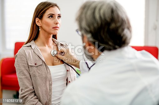 Young woman getting her painful chest examined by a doctor.