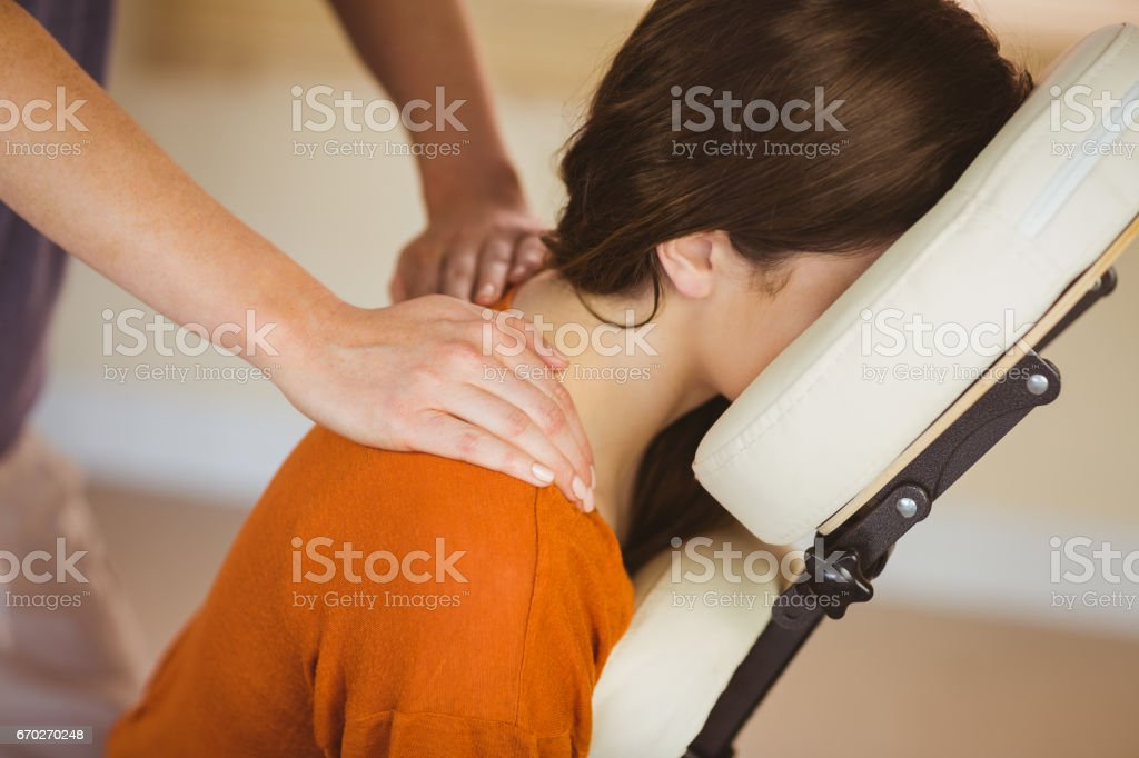 Young woman getting massage in chair stock photo