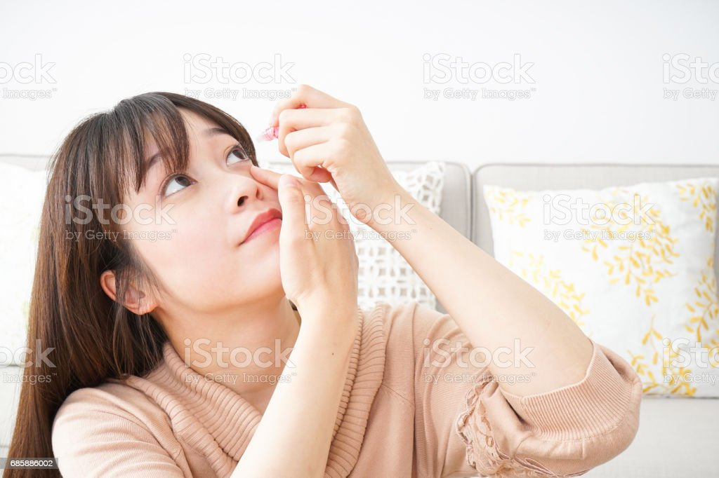 Young woman getting the medicine in the eye